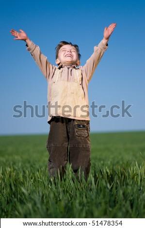 Happy little boy jumping in field against blue sky - stock photo