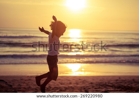 Happy little boy jumping on the beach at the sunset time - stock photo