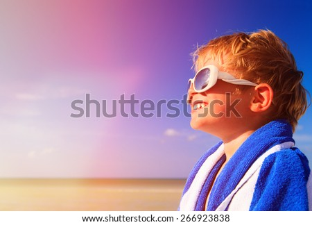 happy little boy laugh wrapped in beach towel on sky, enjoy summer concept - stock photo