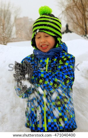 Happy little boy laughing and playing with snow. The child keeps the snow in his hands