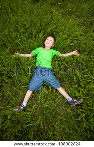 happy little boy laying on the green grass