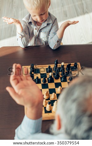 Happy little boy learning to play chess from his grandfather - stock photo