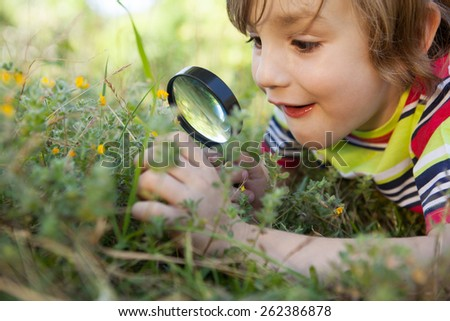 Happy little boy looking through magnifying glass on a sunny day - stock photo