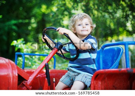 Happy little boy of three years having fun on tractor in summer, outdoors - stock photo