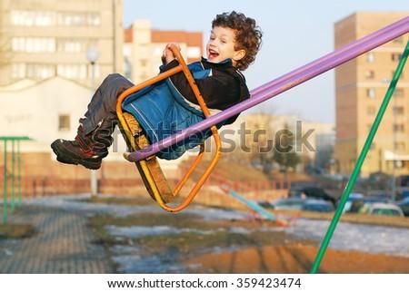 happy little boy on a swing - stock photo