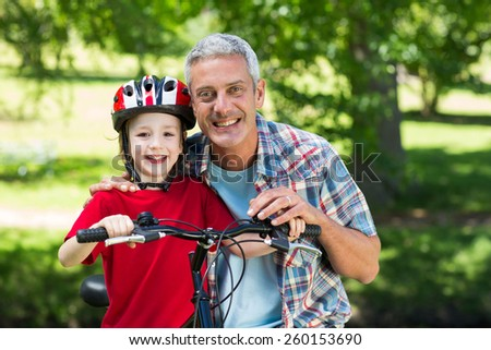 Happy little boy on his bike with his father on a sunny day - stock photo