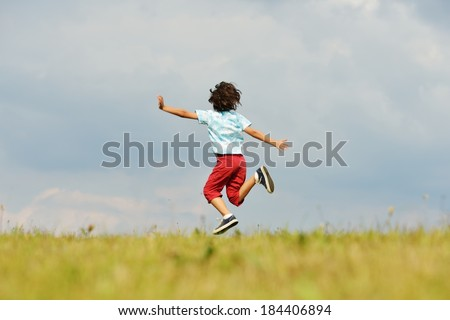 Happy little boy on summer grass meadow in nature jumping