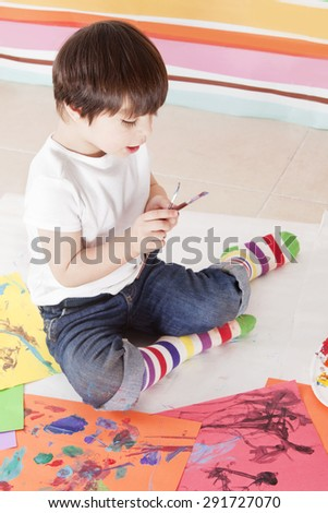 Happy little boy painting in kindergarten - stock photo