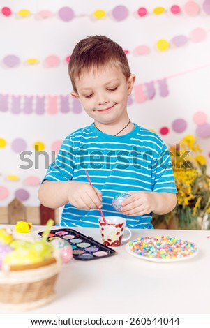 Happy little boy painting the easter eggs - stock photo