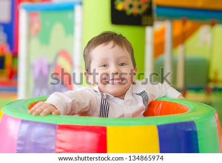 Happy little boy playing in playroom - stock photo
