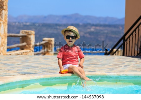 happy little boy playing in swimming pool - stock photo