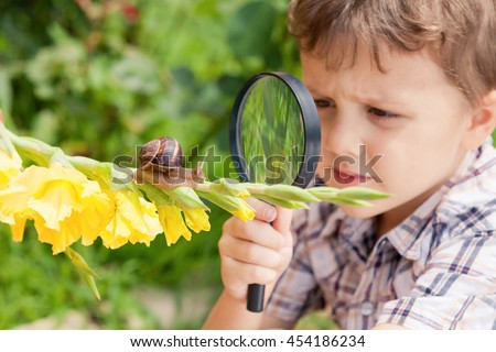 Happy little boy playing in the park with snail at the day time. He having fun on the garden. Concept of the kid is ready to go to school. - stock photo
