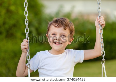 happy little boy playing on playing on the playground at the day time - stock photo