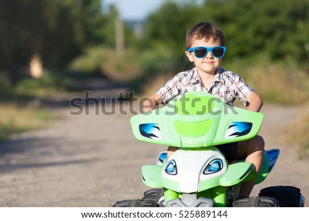 Happy little boy playing on road at the day time. He driving on quad bike in the park. Child having fun on the nature. Concept of happiness.