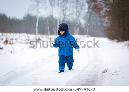 Happy little boy playing outdoor in winter snow. Snowy weather and caucasian child.