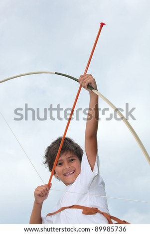 Happy little boy playing with bow and arrow