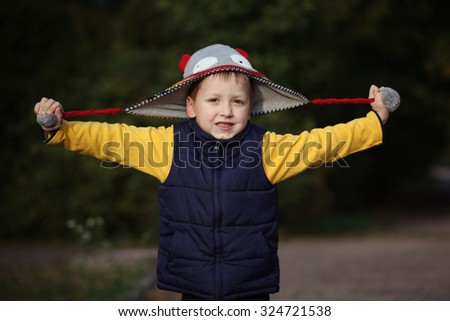 Happy little boy playing with cap  in  autumn park - stock photo