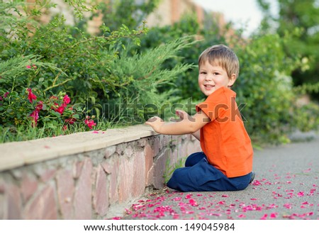 happy little boy playing with flowers - stock photo