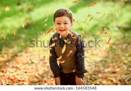 Happy little boy playing with leaves in the park, autumn time - stock photo