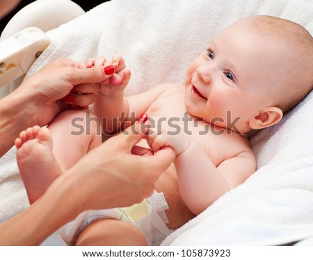 happy little boy playing with mother's hands