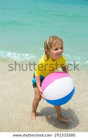 Happy little boy  plays with colorful beach ball - stock photo