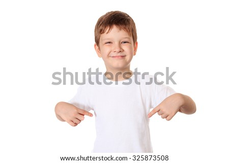 Happy little boy pointing his fingers on a blank t-shirt, a place for your advertising. - stock photo