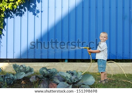 Happy little boy pours water from a hose