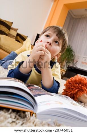 Happy little boy reading open book - stock photo