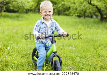 Happy little boy riding learner bike on grass