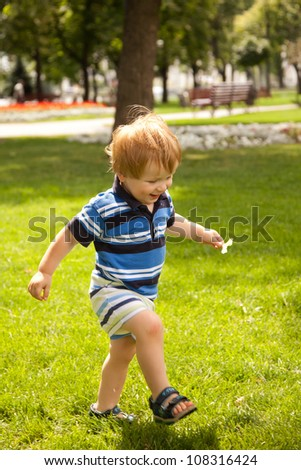 happy little boy running in garden with mouth open - stock photo