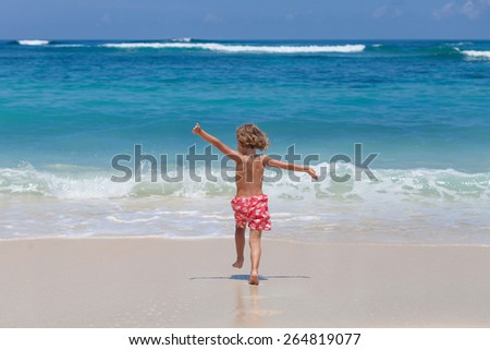 Happy little boy running on the beach at the day time
