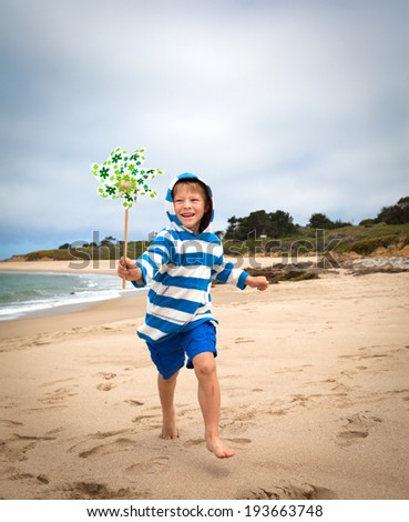 Happy little boy running on the beach with a pinwheel in his hand