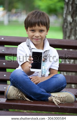 Happy little boy sits on a bench and showing mobile phone screen on a background of summer park