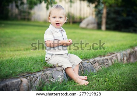 Happy little boy sitting barefoot outdoors on a stone board in Summer.