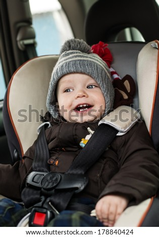 happy little boy sitting in the car seat in the winter