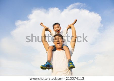 happy little boy  sitting on father's shoulder
