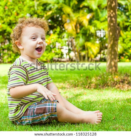 happy little boy sitting on the grass in the garden - stock photo
