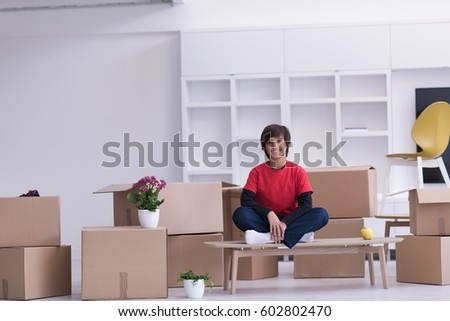 happy little boy sitting on the table with cardboard boxes around him in a new modern home