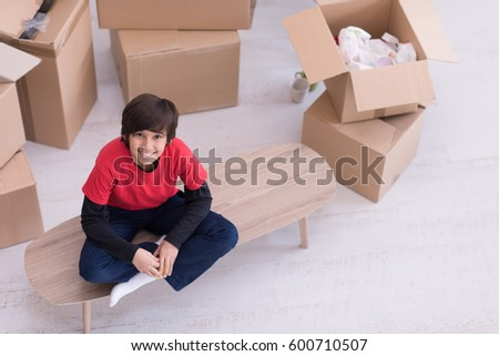 happy little boy sitting on the table with cardboard boxes around him in a new modern home,top view
