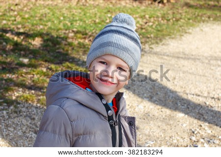 Happy little boy smile in cap at early spring