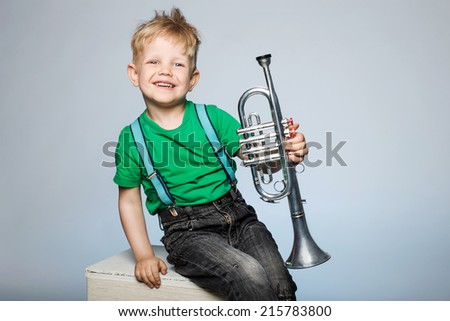 Happy little boy smiling and holding musical instrument - stock photo