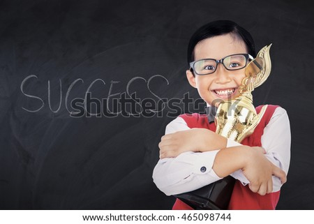 Happy little boy smiling at the camera while holding a trophy in the class with Success word on the blackboard