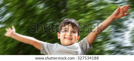 Happy little boy smiling on blurred nature background - stock photo