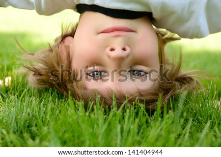 Happy little boy standing upside down on green grass in spring park. - stock photo