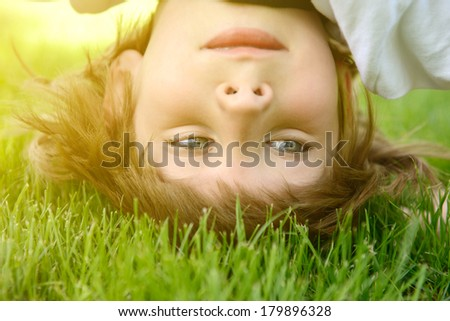 Happy little boy standing upside down on green grass in spring park, toned - stock photo