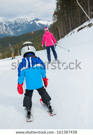 Happy little boy studying to ski in ski goggles and a helmet with his mother - stock photo