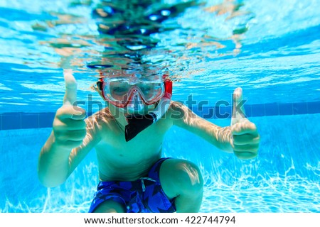 happy little boy swimming underwater with thumbs up