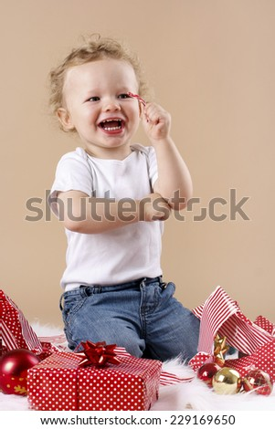 Happy little boy unwrapping christmas presents