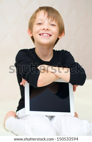 Happy little boy using tablet computer indoors - stock photo