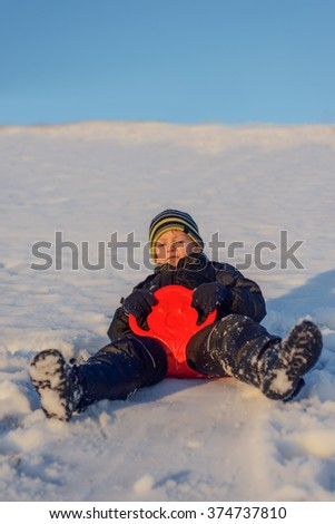 Happy little boy warmly wrapped in winter clothing having fun in fresh white winter snow in evening light as he grins at the camera